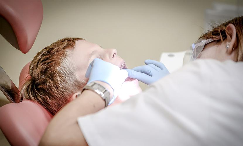 Zahnärztin behandelt Kind mit Sandstrahlgerät dental